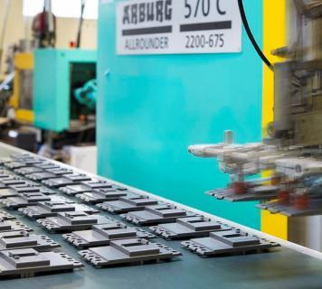 l'immagine di una produzione in plastica con pressa e robot